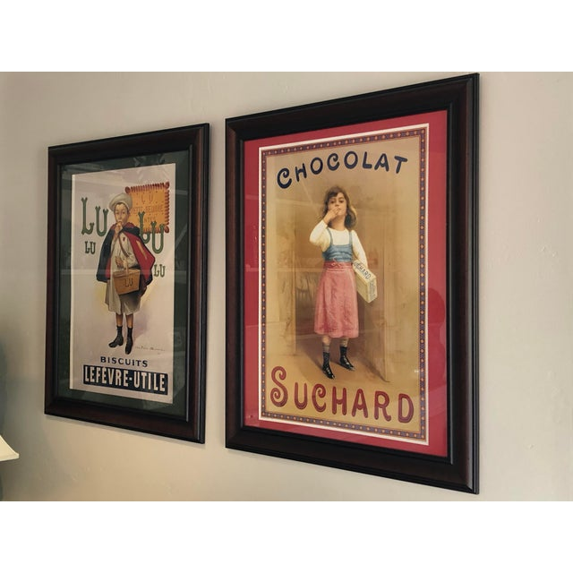 A charming print of French chocolate advertisement custom framed with a red mat, warm walnut wood and covered in UV...