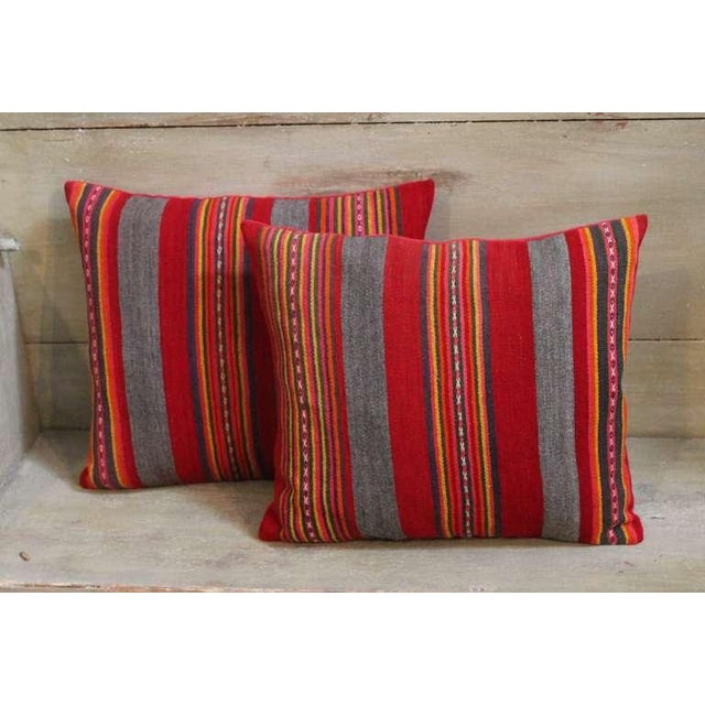 This unusual pair of striped wool pillows is constructed from early 20th century fabric and feature an interesting color...