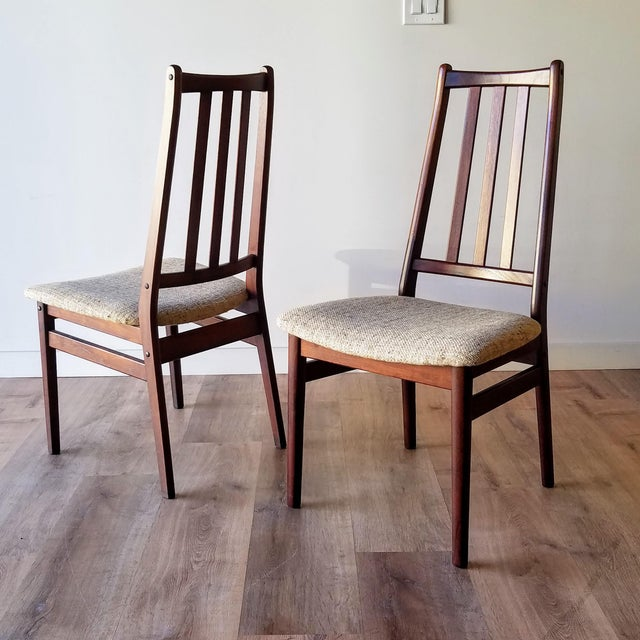 A set of eight Danish Mid-Century Modern dining chairs. These high-back chairs have a gently angled backrest with three...