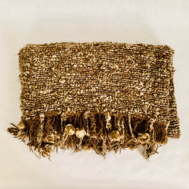 Chunky knit pom pom rug in tones of speckled brown and cream adds texture and coziness to your space. Looks great at the...