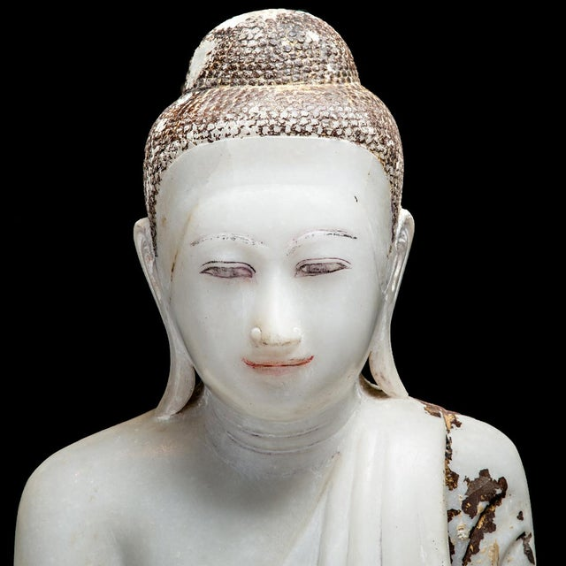 This marble statue of the buddha demonstrates the high degree of artistic refinement achieved through the artistic...