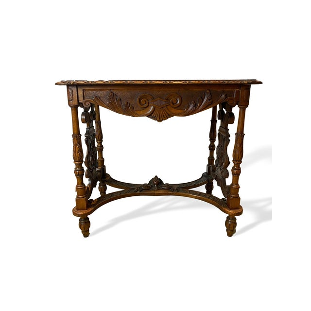 Hand carved walnut center table, Italian, circa 1880, profusely hand carved, the shaped top carved with a central motif of...