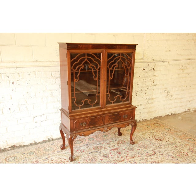 Offering a beautiful French Chippendale china of dining cabinet. The piece has very nice carved details and a flame...