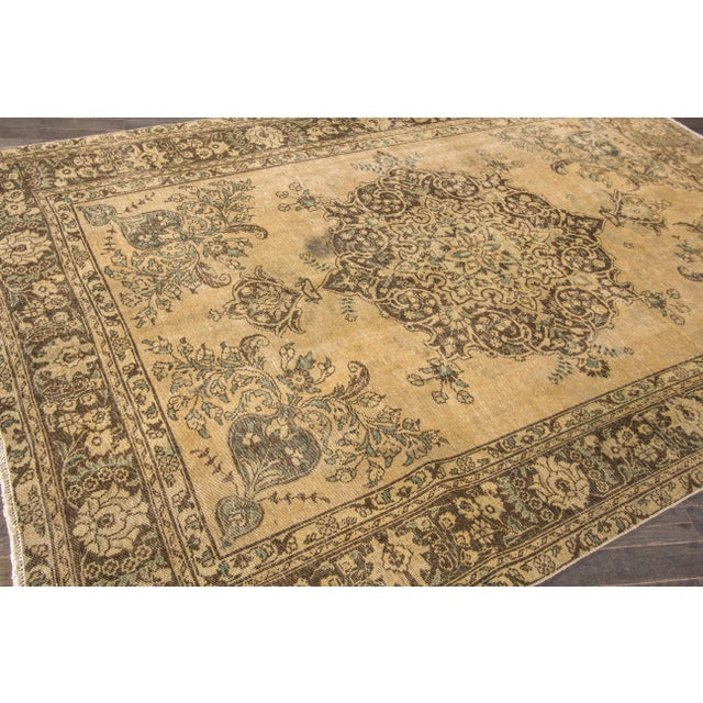 Vintage hand-knotted Tabriz rug with a medallion design, distressed areas and small stain due to age and use.. This piece...