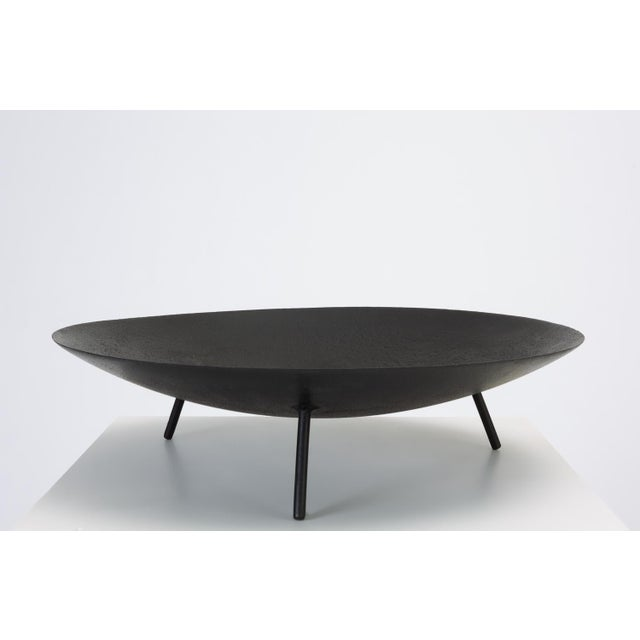 A Mid-Century Modern fire pit or brazier in wrought iron with three splayed legs. The piece has a Fine edge and a thicker...