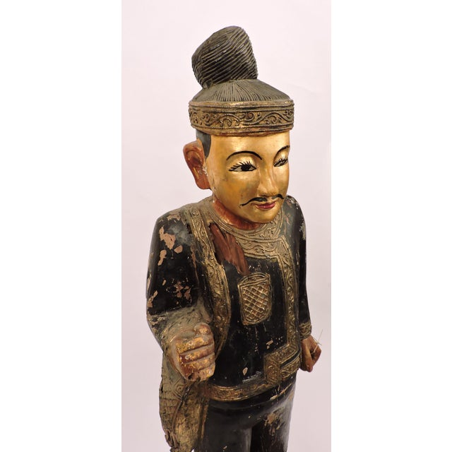 Nats are spirits worshipped in Buddhist Burma. This one has been on a journey, dressed in black and gold atop a rotted...