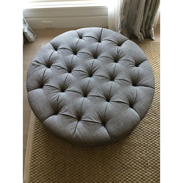 Upholstered ottoman in Romo grey week fabric. Tufted with buttons and skirted base. The ottoman has casters (one is...