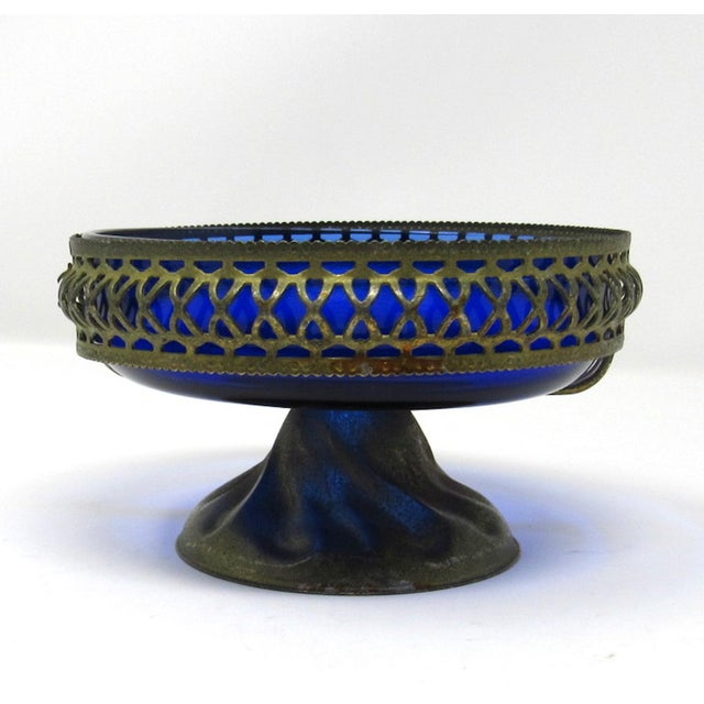 A 1920s cobalt blue pressed glass bowl liner inside a pierced metal pedestal stand. The bowl can be used an open sugar...