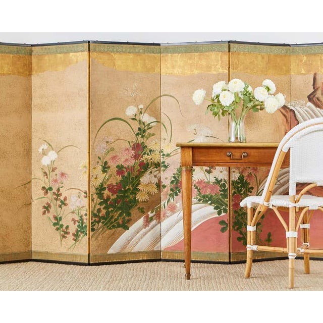 Impressive Japanese six panel Meiji period screen featuring chrysanthemums with a waterfall landscape behind. Late 19th...