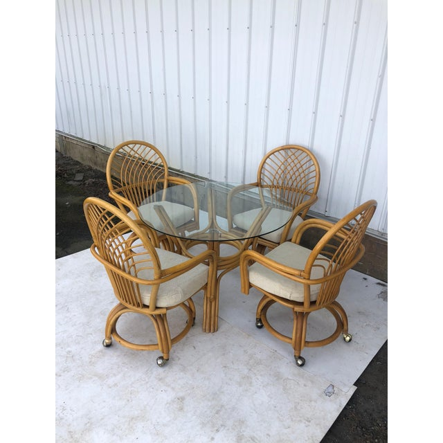 This vintage rattan dinette set features four wheeled chairs with removable cushions and a glass top table. Table...
