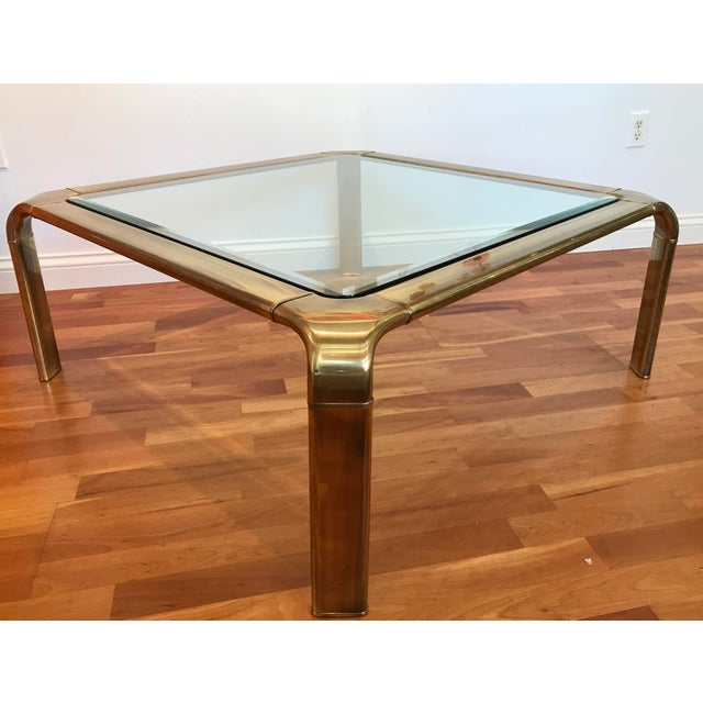 Sleek modern lines of this aged brass and glass cocktail table for Mastercraft by Baker Furniture was created in the...