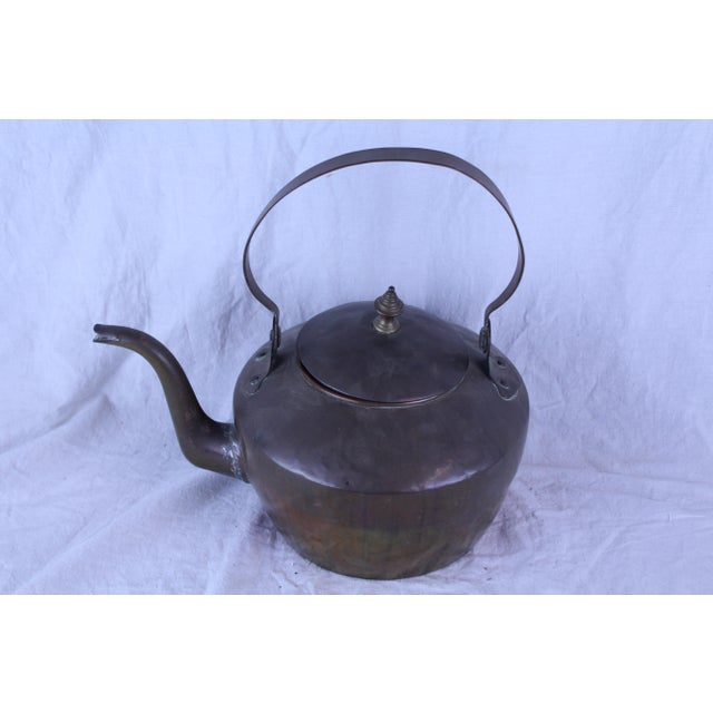 Antique copper tea kettle with large handle and removable lid. Made in the early 20th century.