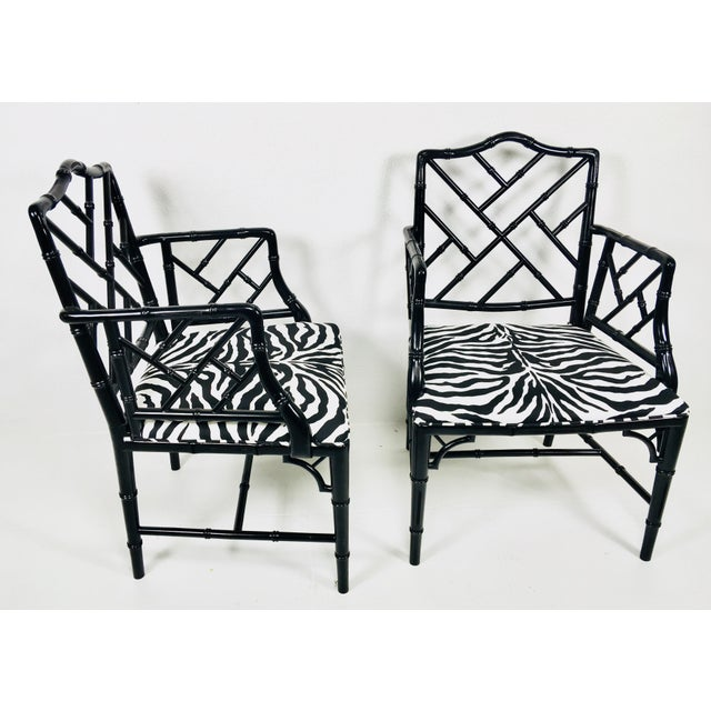 This is a pair of Chinese Chippendale style chairs. In a black finish with with a faux zebra pattern upholstered seat. The...