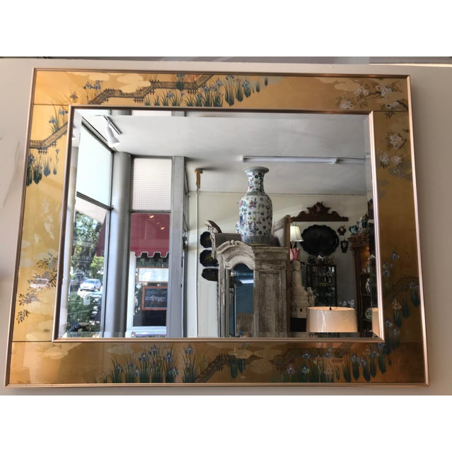 A contemporary beveled mirror with a path, florals and blossoms on a gold background.