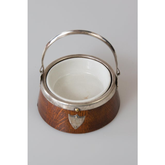 A rare English oak jam jar or mustard pot with lovely silver-plated details and a porcelain liner, circa 1920. This...