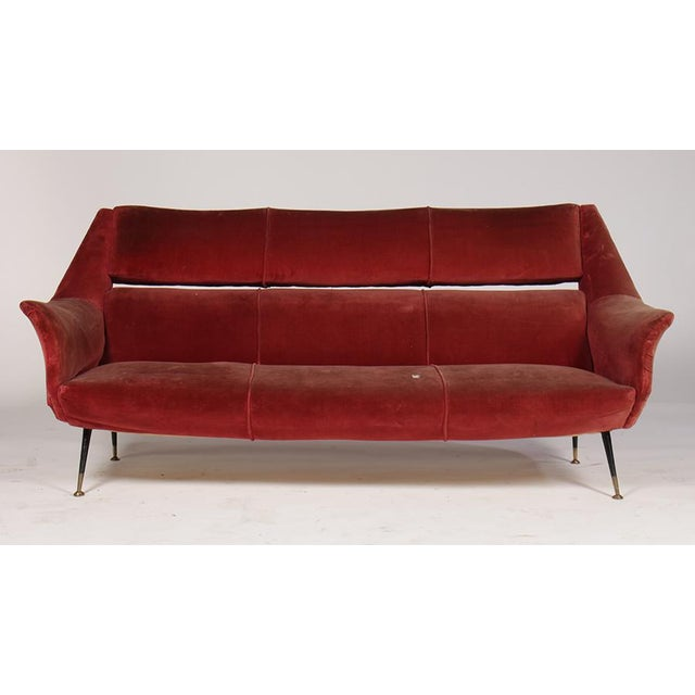 An Italian mid-century modern sofa has flared arms and resting on bronze tipped iron legs circa 1960