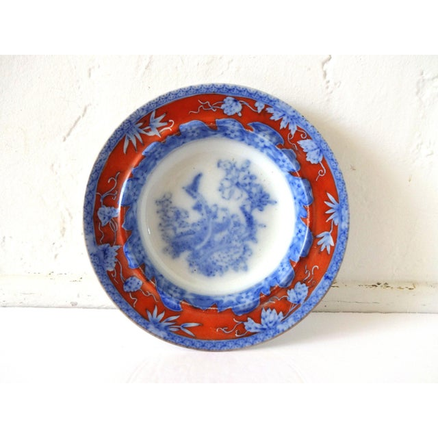 """An antique, early flow blue deep plate or bowl, very large, featuring a detailed but """"flowed"""" scene of birds and trees in..."""