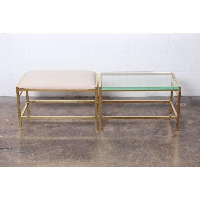 A brass bench with upholstered leather top and matching brass table with glass top. Designed by Edward Wormley for Dunbar....