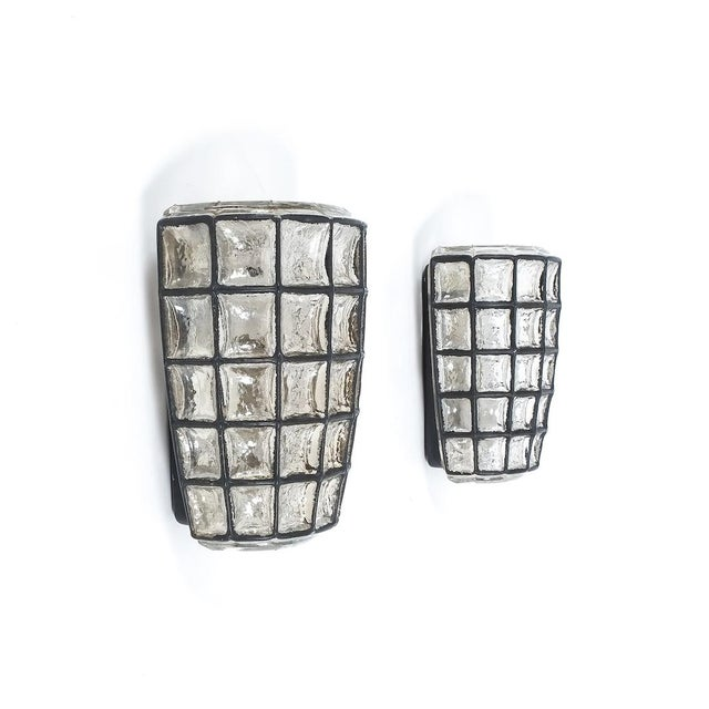 Pair of thick glass wall lights with black accents by Limburg, 1960s. Each holds a single bulb per light 60W max. The...