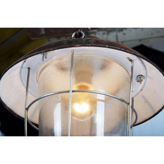 This industrial vintage factory hanging lamp was designed in the 1970s and comes from Austria. It consists of steel and...