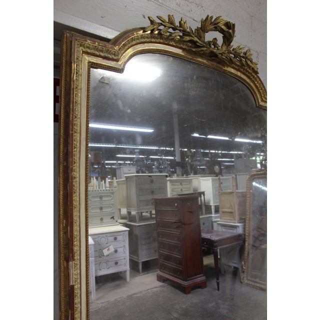 Louis XVI antique, giltwood mirror with original glass and gold finish. Framed with gadrooned molding and rocaille mounts,...