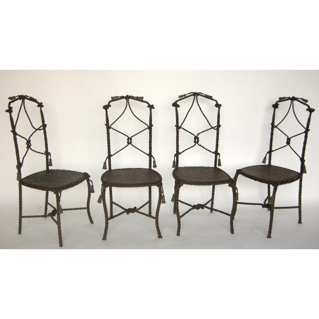 Set of four whimsical wrought iron chairs with traces of old paint. Iron tassels.