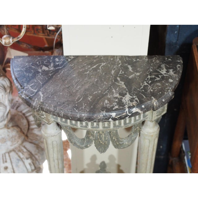 Gray and white marble top over a carved greek key design apron with swags. Two fluted tapered legs meet the stretcher...