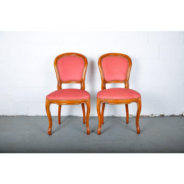 Pair of Vintage French Louis XV style dining chairs made of solid maple wood. The chairs feature a solid wood frame, hand-...