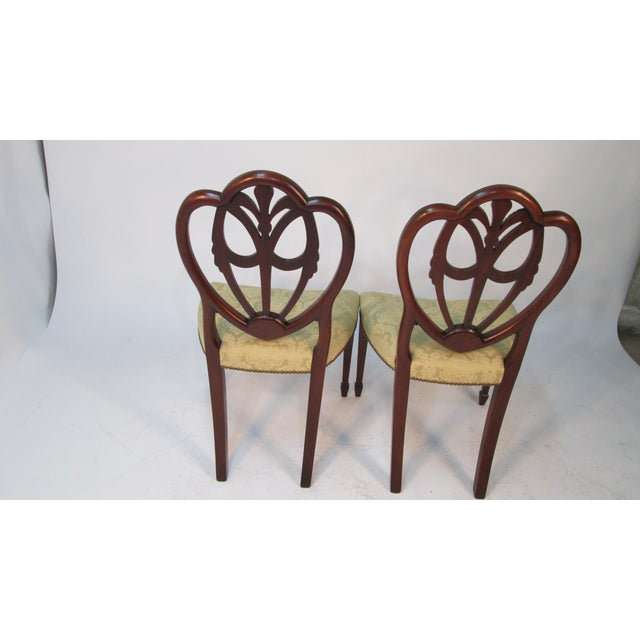A set of custom made soldi mahogany shield back dining chairs attributed to Old Colony of Boston MA. Heavily carved child...