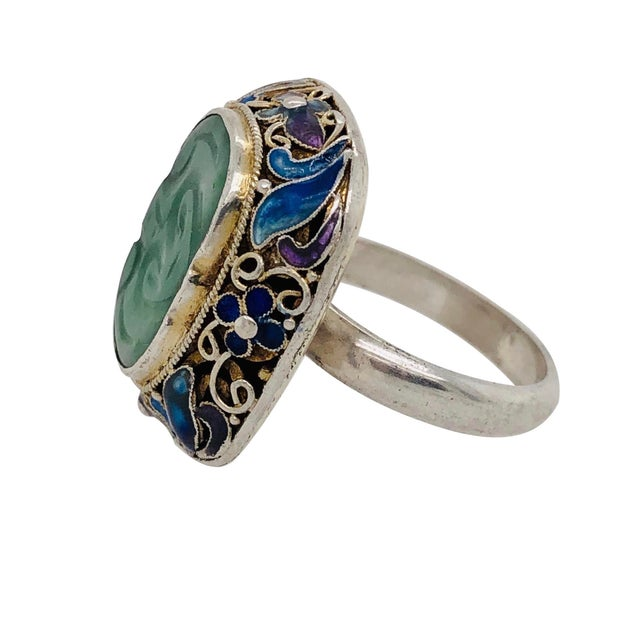 A vintage Chinese silver ring with a carved jade mounted in an ornate silver and enamel filigree bezel. The top of the...