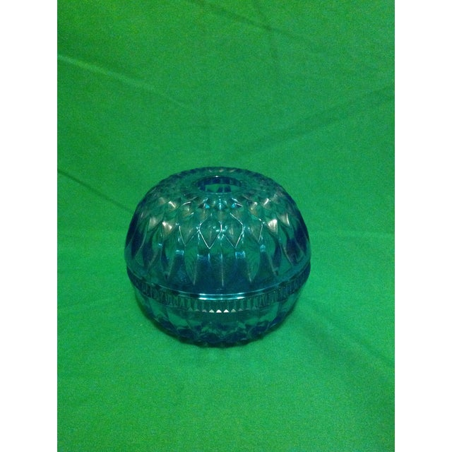 An elegant blue glass globe candleholder that would look excellent as a soft accent in a beach style space or oceanic...