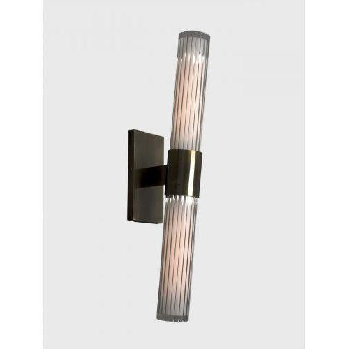 The Dixie Wall Sconce by Trella is shown in medium brown brass with two light sources each with internally fluted outer...