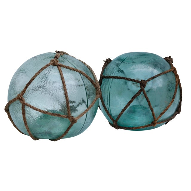 A set of three vintage glass fishing floats made of hand blown glass, tied with original rope netting. Actual floats...