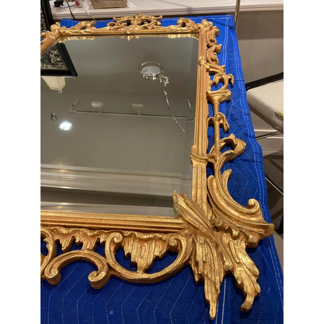 """Vintage gilded mirror with beautiful ornate wood details. Has roses and leaves on the top corners and has """"ice shaped..."""