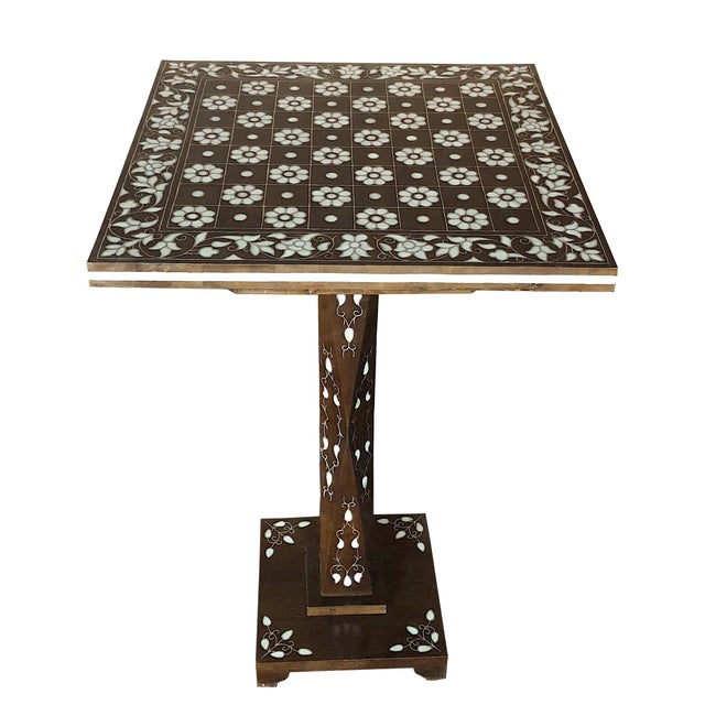 Set of elegant pedestal and chess board table of ebonized walnut wood, inlaid with mother-of-pearl and metal. The chess...