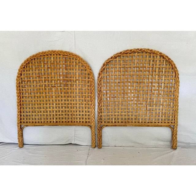 Vintage pair of woven rattan/wicker twin headboards. Thin reeds woven together on an arched frame with braided trim.