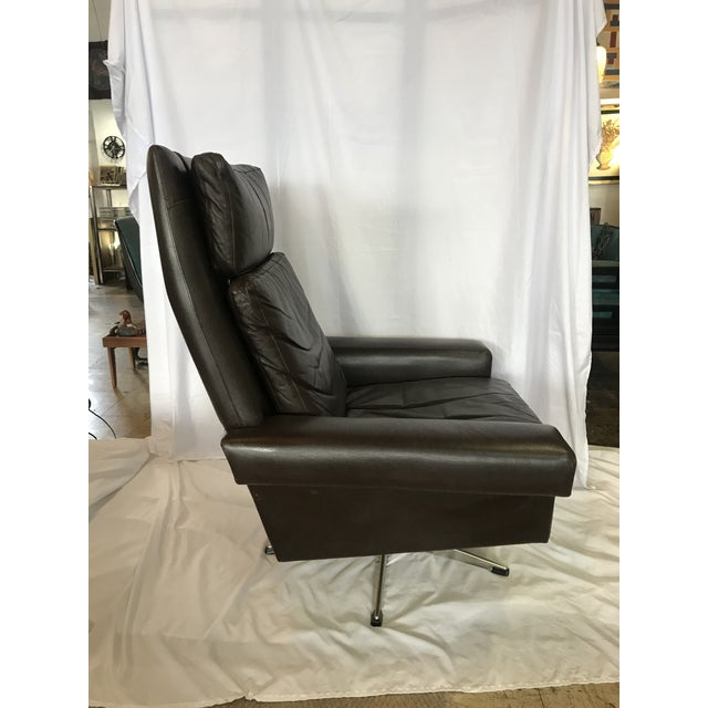 Handsome high-back dark brown leather swivel chair with separate head rest, back and seat cushions and metal base.
