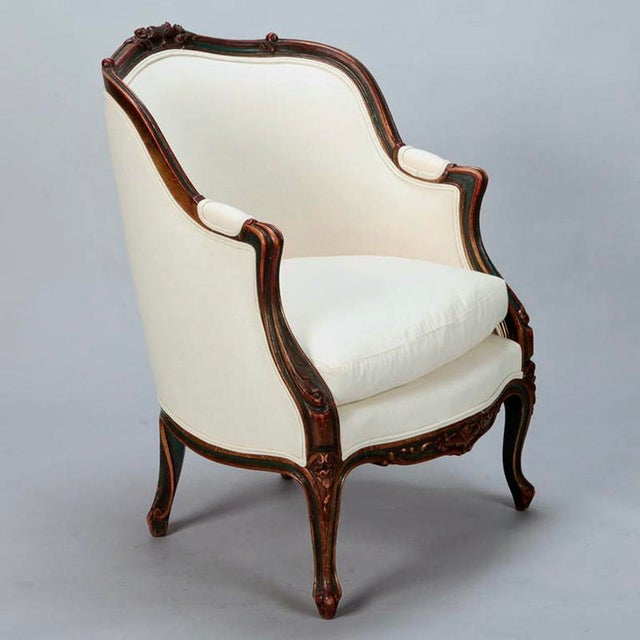 Circa 1900 French bergere arm chair featuring a finely carved solid wood frame. Classic rounded barrel back, padded arm...