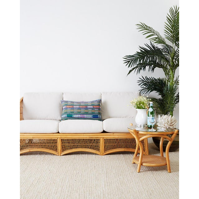 Sculptural Mid-Century Modern three-seat sofa or settee. Constructed from a bamboo rattan frame reinforced with wooden...