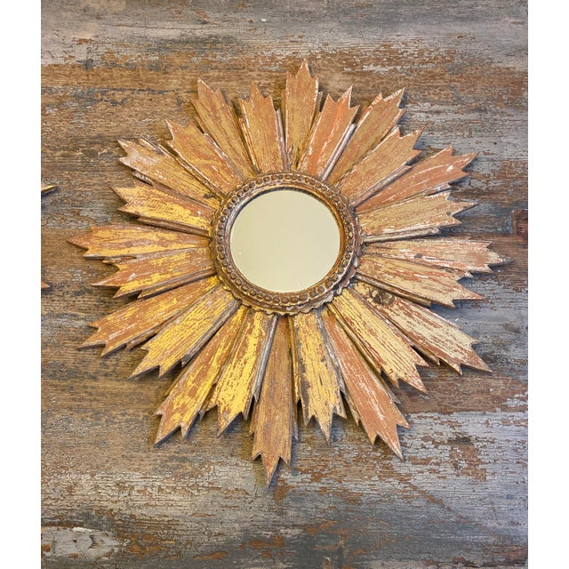 Stylish pair of Tuscan sunburst wall mirrors, featuring graduated carved wood sun rays, a gold and rust hand made patina,...