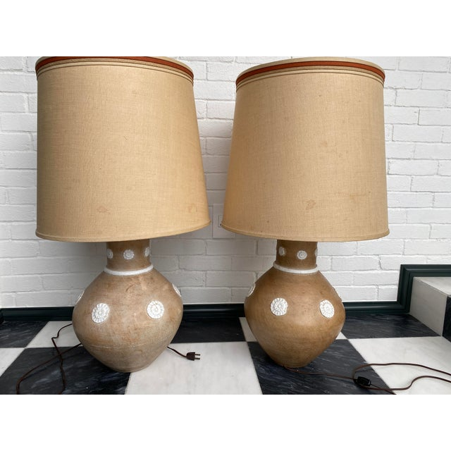 Pair of fine sand-colored midcentury Italian ceramic lamps in an ovoid form. Both lamps are signed on undersides of...
