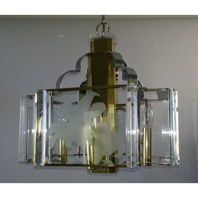 This is a beautiful vintage mid-century modern style chandelier by Fredrick Ramond made of chrome, lucite, and four glass...