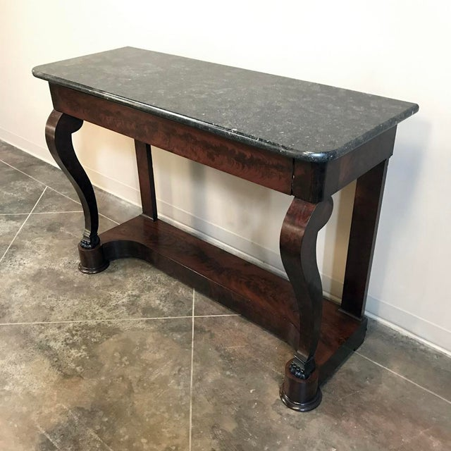 19th Century French Louis Philippe Marble Top Mahogany Console features the tailored lines for which the style has...