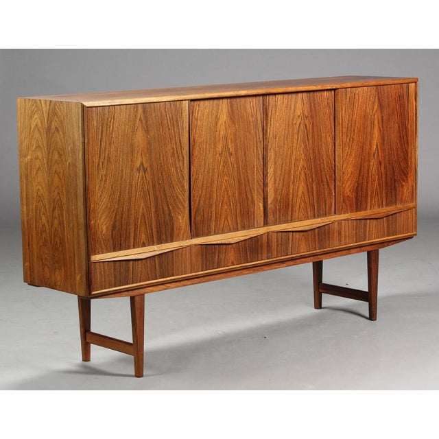 High rosewood sideboard by EW Bach. Front with sliding doors, behind which are shelves, drawers and mirrors. Manufactured...