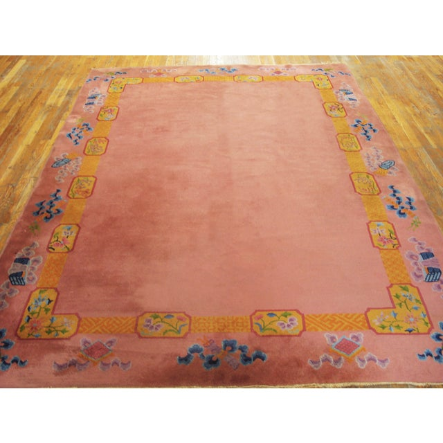 Antique Chinese Art Deco Rug with a pink background and patterned border.