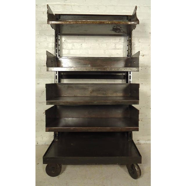 Industrial metal shelving unit featuring five levels, four adjustable in height on sturdy wheels. Please confirm item...