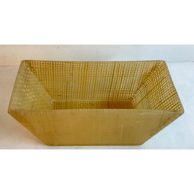 Unique Mid Century Planter made of hard translucent plastic with pieces of twine inside.