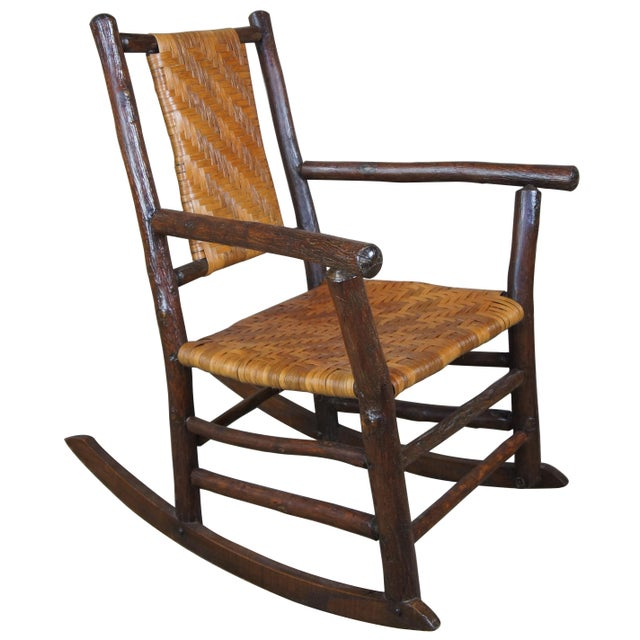 Pre 1930s rocking chair by The Rustic Hickory Furniture Company. Features a primitve log and rattan style with flaired...