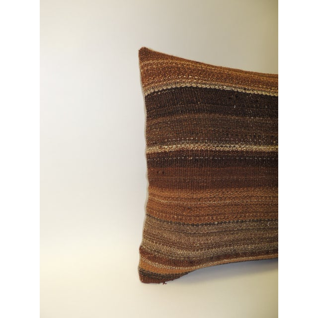 Brown woven Turkish stripe decorative bolster pillow. Pillow is backed with tan woven linen. Zipper closure. Size: 15 x 24...