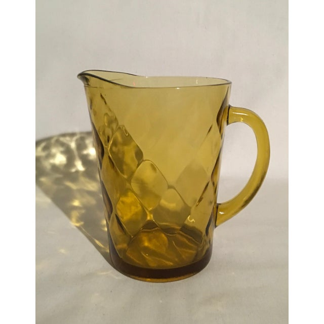 Offering a 1970s Hazel-Altlas amber pressed-glass pitcher with embossed diamond pattern. The pitcher stands 8 inches tall,...